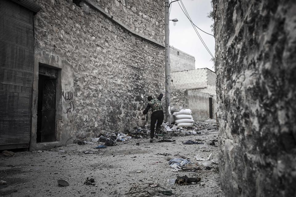 In this Wednesday, Oct. 24, 2012 photo, a rebel fighter belonging to the Liwa Al Tawhid group throws a grenade towards government troops during clashes at the Moaskar front line, one of the battlefields in Karmal Jabl neighborhood, in Aleppo, Syria. (AP Photo/Narciso Contreras).