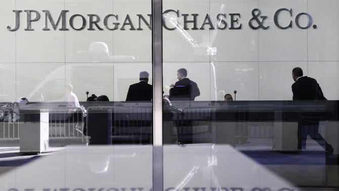 FILE - In this May 11, 2012 file photo, people stand in the lobby of JPMorgan Chase headquarters in New York. Moody's Investors Service on Thursday, June 21, 2012 lowered the credit ratings of 15 the world's largest banks late Thursday, including JPMorgan Chase, Bank of America,  and Goldman Sachs, saying their long-term prospects for profitability and growth are shrinking. (AP Photo/Mark Lennihan, File)