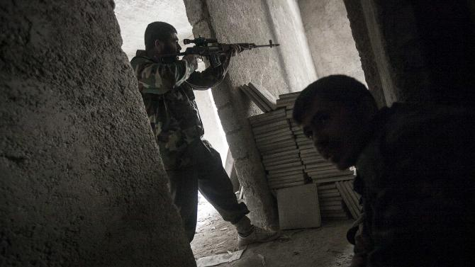 In this Friday, Dec. 07, 2012 photo, a Syrian rebel aims toward troops loyal to President Bashar Assad during clashes in Aleppo, Syria, Friday. As fears grow in the West that Assad will unleash chemical weapons as an act of desperation, NATO moved forward Thursday with its plan to place Patriot missiles and troops along Syria's border with Turkey to protect against potential attacks. (AP Photo/Narciso Contreras)
