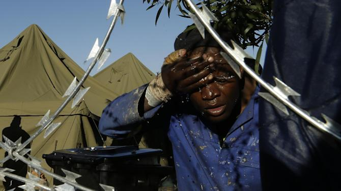 A man washes his face outside a shelter for displaced foreigners in east of Johannesburg, South Africa, Tuesday, April 21, 2015. The South African army has been deployed to areas in that remain volatile after a spate of attacks targeting immigrants, the defense minister announced on Tuesday. (AP Photo/Themba Hadebe)