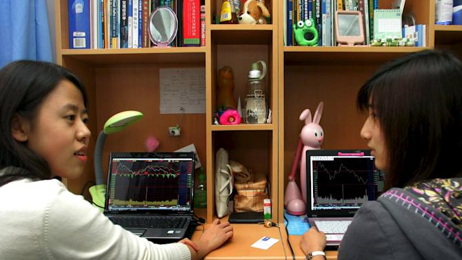 Students sit in front of laptop screens showing stock information at their dormitory, in Beijing