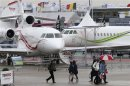 Visitors attend the first day of the rain-soaked 50th Paris Air Show, at the Le Bourget airport near Paris