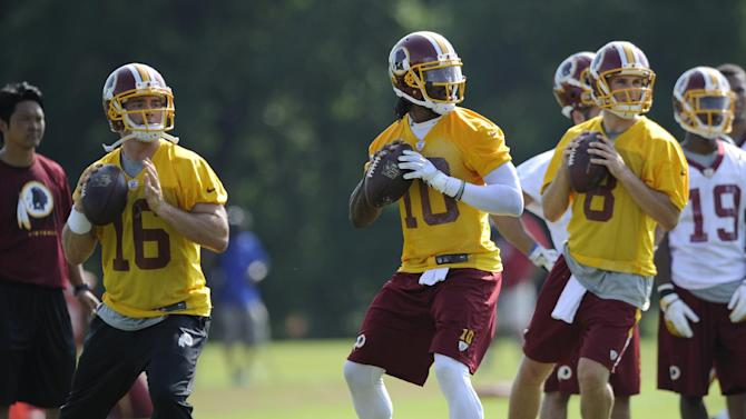 Washington Redskins quarterbacks Robert Griffin III (10), Colt McCoy (16) and Kirk Cousins (8) drop back to pass during NFL football minicamp, Tuesday, June 17, 2014, in Ashburn, Va
