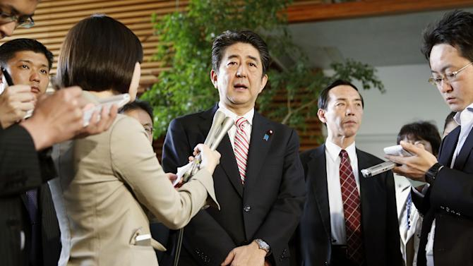 Japanese Prime Minister Shinzo Abe, center, speaks to the media before his departure for Singapore at the prime minister's official residence in Tokyo Friday, May 30, 2014. China's moves to assert its territorial claims in the South China Sea are giving fresh impetus to Japanese plans to play a bigger role in regional security, adding to the growing strains between the two Asian rivals. Abe is likely to stress Japan's commitment to regional stability in a speech to Asia-Pacific defense ministers in Singapore on Friday night.(AP Photo/Kyodo News) JAPAN OUT, CREDIT MANDATORY