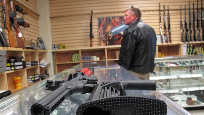 "This Feb. 1, 2013 photo shows a ""bump stock"" beside a disassembled .22-caliber rifle at North Raleigh Guns in Raleigh, N.C. The accessory devices, which legally allow a semiautomatic rifle to fire like a real machine gun, are among 157 weapons or accessories targeted by a proposed federal ban. (AP Photo/Allen Breed)"