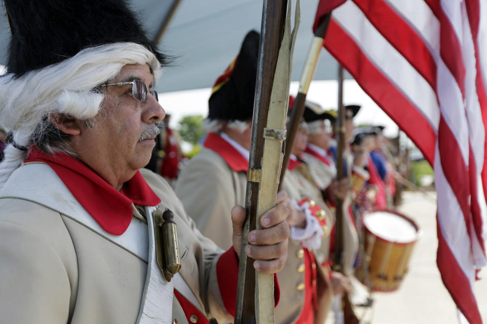 Henry Alvarado, a member of the Granaderos y Damas de Galvez, stands at attention with other living history members during the national anthem during a Fourth of July Patriotic Ceremony at Fort Sam Houston National Cemetery, Thursday, July 4, 2013, in San Antonio. (AP Photo/Eric Gay)