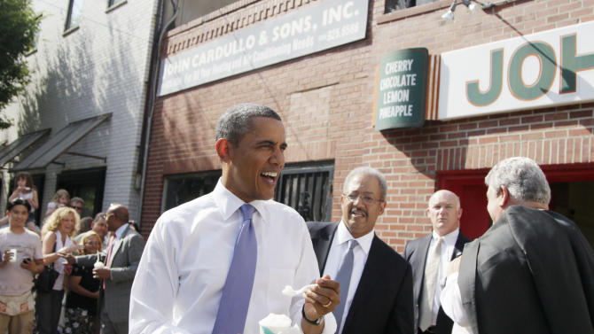 President Barack Obama eats a lemon water ice at John's Water Ice, Thursday, June 30, 2011, in Philadelphia. Standing right is Rep. Robert Brady, D-Pa., and left behind Obama is Rep. Chaka Fattah, D-Pa. (AP Photo/Carolyn Kaster)