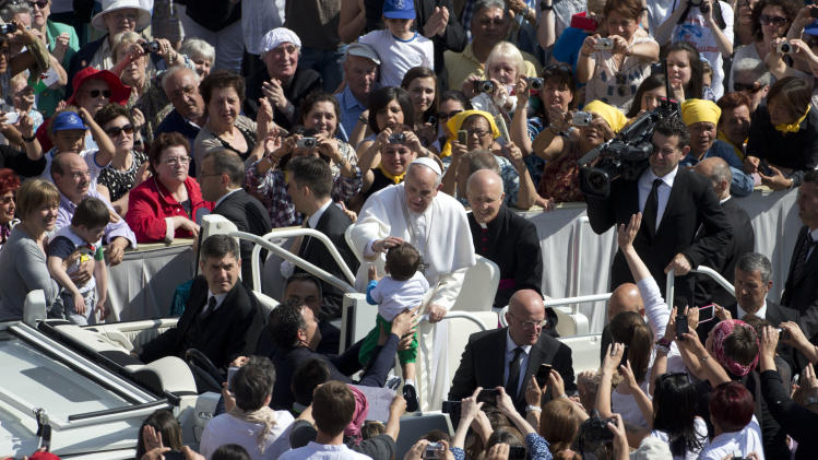 Pope Francis caresses a child as he is driven through the crowd in St. Peter's Square at the Vatican during his weekly general audience, Wednesday, May 8, 2013. (AP Photo/Andrew Medichini)