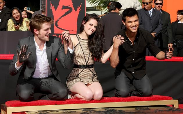Robert, Kristen and Taylor hold (mucky!) hands at their hand and footprint ceremony in Los Angeles.