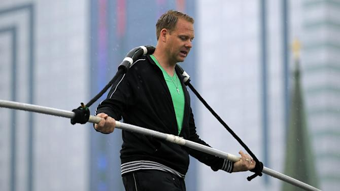 FILE - This May 16, 2012 photo shows Nik Wallenda performing a walk on a tightrope in the rain during training for his walk over Niagara Falls in Niagara Falls, N.Y. Wallenda can't visit a new place without envisioning a wire strung high above his head: Linking buildings, landmarks, nations. Even as a 6-year-old at Niagara Falls with his parents, he pictured walking a tightrope over the raging, whitewater maw. Now 33, he's ready to live out that childhood fantasy when he attempts Friday, June 15, 2012 to become the first person ever to walk a tightrope directly over the brink of Niagara Falls. (AP Photo/David Duprey)