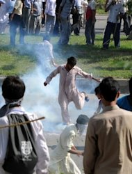 A Pakistani Muslim protester kicks a tear gas shell as demonstrators attempt to reach the US embassy during a protest against an anti-Islam film in Islamabad. Thousands of Pakistanis attempted to storm Islamabad's diplomatic enclave on Thursday, as anger mounted across the Muslim world over perceived Western insults to the Prophet Mohammed