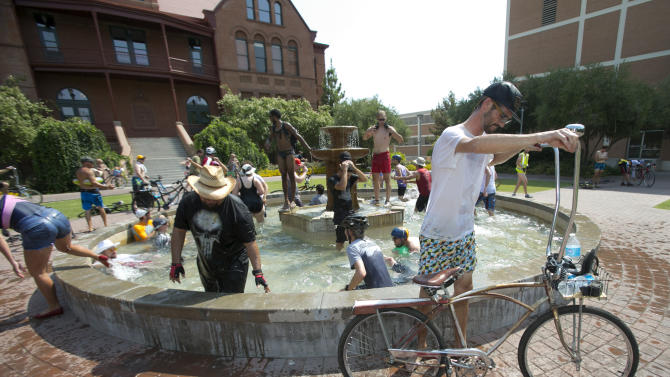 Brian Stolfa of Scottsdale, Ariz. gets on his bike after cooling off in the fountain in front of Old Main on the Arizona State University campus in Tempe, Ariz. during the Tempe Bicycle Action Group swimsuit ride on Saturday, June 29, 2013. About 100 cyclists biked around the city cooling off in pools and fountains. (AP Photo/The Arizona Republic, David Wallace)