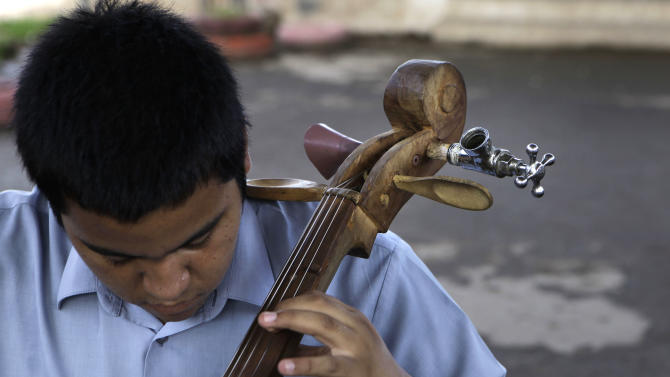 """In this Dec. 11, 2012 photo, a young musician tunes his cello, made from recycled materials, during a practice session with """"The Orchestra of Instruments Recycled From Cateura"""" in Cateura, a vast landfill outside Paraguay's capital of Asuncion, Paraguay. Children from the orchestra use instruments fashioned out of recycled materials taken from a landfill where their parents eke out livings as trash-pickers, and about 20 of them regularly perform the music of Beethoven and Mozart, Henry Mancini and the Beatles.  (AP Photo/Jorge Saenz)"""