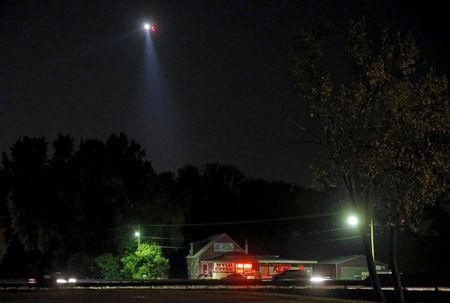 Police helicopters use search lights on the wooded areas for the killers of slain Fox Lake Police Lieutenant Charles Joseph Gliniewicz in Fox Lake