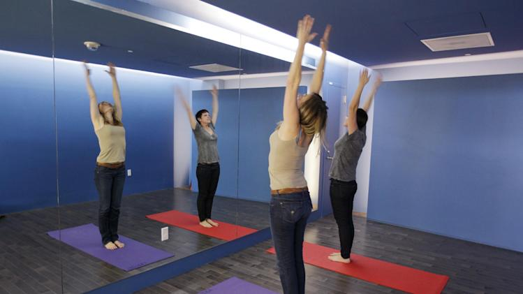 In this Friday, Jan. 27, 2012 photo, travelers Maria Poole, left, and Lindsey Shepard practice yoga at San Francisco International Airport's new Yoga Room, in San Francisco. The quiet, dimly lit studio officially opened last week in a former storage room just past the security checkpoint at SFO's Terminal 2. Airport officials believe the 150-square-foot room with mirrored walls is the world's first airport yoga studio, said spokesman Mike McCarron. (AP Photo/Paul Sakuma)