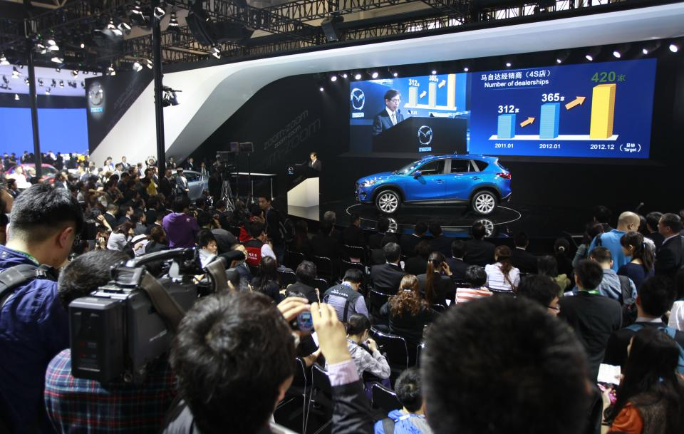Media attend a press conference by Mazda as the company launches new SUV CX-5 at the Beijing International Auto Exhibition in Beijing, China, Monday, April 23, 2012.  (AP Photo/ Vincent Thian)