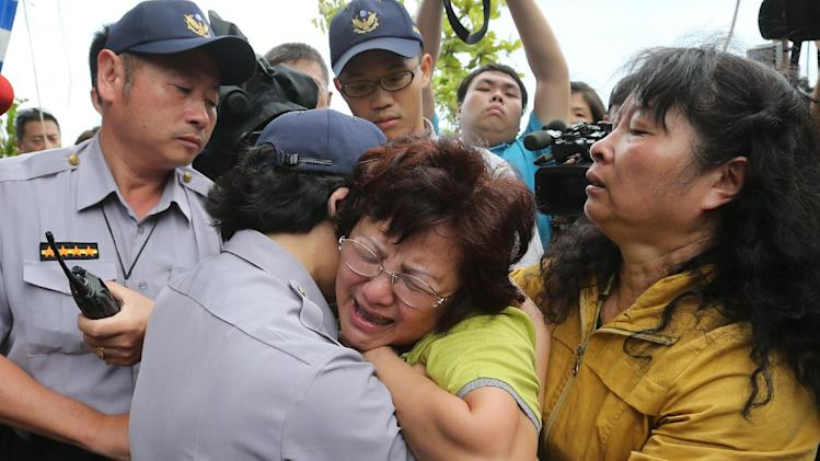 A relative of a passenger onboard the TransAsia Airways Flight GE222 that crashed on the Taiwanese island of Penghu, cries at a funeral parlor in Penghu, Taiwan, Thursday, July 24, 2014. The plane attempting to land in stormy weather crashed on the island late Wednesday, killing dozens of people and wrecking houses and cars on the ground. (AP Photo) TAIWAN OUT