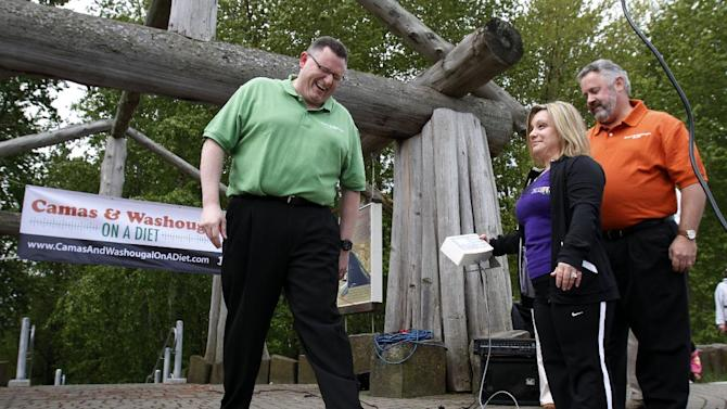 """Camas Mayor Scott Higgins, left, steps on the scales as Washougal Mayor Sean Guard, right, and health coach Michelle Clark watch during their weigh-in in Washougal, Wash., Wednesday, May 2, 2012.  The mayors of the two neighboring Washington state towns on the banks of the Columbia River are embarking on a """"Biggest Loser"""" style contest to see which of the two communities can lose the most weight in 12 months. (AP Photo/Don Ryan)"""