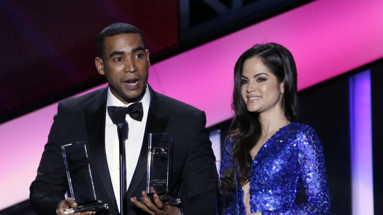 Singer Don Omar, left, and Natty Natasha hold the latin rhythm song of the year award at the Latin Billboard Awards in Coral Gables, Fla., Thursday April 25, 2013. (AP Photo/Alan Diaz)