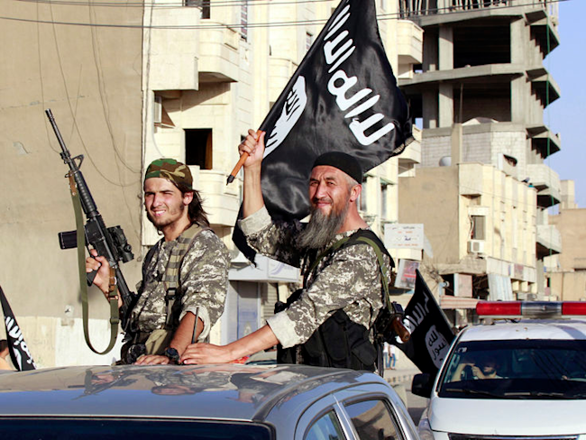 Islamic State fighters wave flags as they take part in a military parade along the streets of northern Raqqa province, Syria June 30, 2014. REUTERS/St...