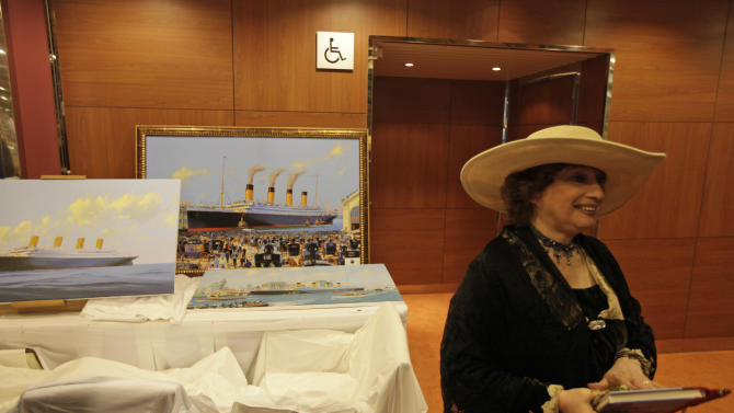 A passenger of the MS Balmoral Titanic memorial cruise ship stands next to paintings depicting the Titanic, aboard the MS Balmoral Titanic memorial cruise ship, in the Atlantic Ocean, Tuesday, April 10, 2012. Nearly 100 years after the Titanic went down, the cruise with the same number of passengers aboard is setting sail to retrace the ship's voyage, including a visit to the location where it sank. The Titanic Memorial Cruise departed Sunday, April 8, from Southampton, England, where the Titanic left on its maiden voyage and the 12-night cruise will commemorate the 100th anniversary of the sinking of the White Star liner. With some 1,300 passengers aboard, the MS Balmoral will follow the same route as the Titanic and organizers are trying to recreate the onboard experience minus the disaster from the food to a band playing music from that era. (AP Photo/Lefteris Pitarakis)