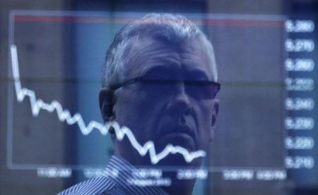 An office worker is reflected in the window of the Australian Securities Exchange building in Sydney