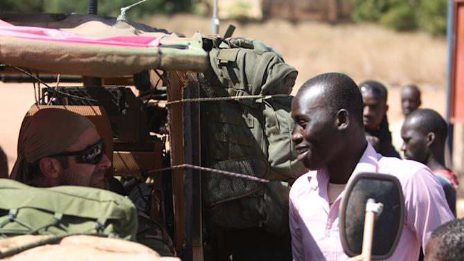A resident of San in central Mali talks with a French soldier in his vehicle as French troops pass through en route to Sevare, Mali, Friday, Jan. 18, 2013. French forces encircled a key Malian town on Friday to stop radical Islamists from striking closer to the capital, a French official said. The move to surround Diabaly came as French and Malian authorities said they had retaken Konna, the central city whose capture prompted the French military intervention last week.(AP Photo/Harouna Traore)
