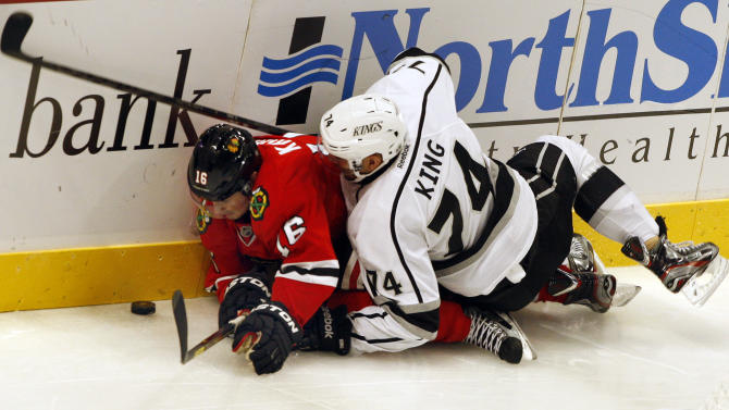 Los Angels Kings' Dwight KIng (74) and Chicago Blackhawks' Marcus Kruger (16) go hard into the boards in the third period of an NHL hockey game on Sunday, Feb. 17, 2013, in Chicago. The Blackhawks won 3-2. (AP Photo/John Smierciak)