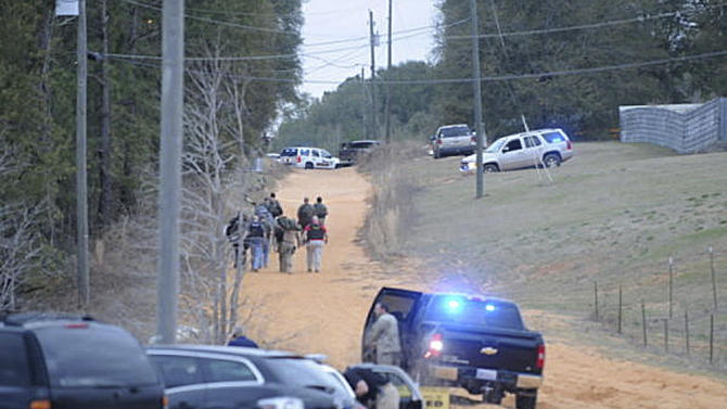 In this Tuesday, Jan 29, 2013 photo, law enforcement officers walk up the road toward a home where a school bus shooting suspect was hiding inside a bunker late Tuesday. Police, SWAT teams and negotiators were at a rural property where a man was believed to be holed up in a homemade bunker Wednesday, HAN 30, 2013 after fatally shooting the driver of a school bus and fleeing with a 6-year-old child passenger, authorities said. The man boarded the stopped school bus in the town of Midland City on Tuesday afternoon and shot the driver when he refused to let the child off the bus. The bus driver died. (AP Photo/The Dothan Eagle, Danny Tindell)