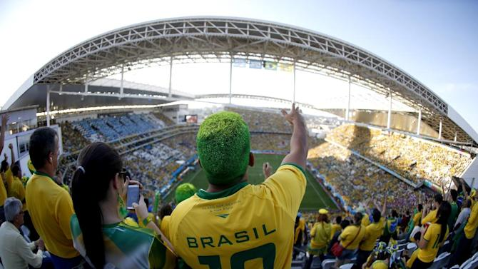 """FILE - In this June 12, 2014 file photo taken with a fisheye lens, a Brazil supporter attends the World Cup opening match between Brazil and Croatia at Itaquerao Stadium in Sao Paulo, Brazil. FIFA's number two official has said he's """"amazed"""" by the levels of drunkenness in Brazil's World Cup stadiums, reviving a debate over whether alcohol sales should have been allowed at matches in the first place. (AP Photo/Julio Cortez, File)"""