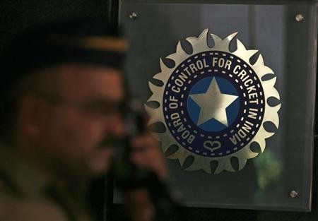 A policeman walks past logo of BCCI in Mumbai