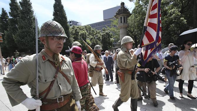 Japanese men clad in outdated military costume march in to pay respects to the country's war dead at the Yasukuni Shrine in Tokyo, Friday, Aug. 15, 2014. Japan marks the 69th anniversary of its surrender in World War II on Aug. 15. (AP Photo/Koji Sasahara)