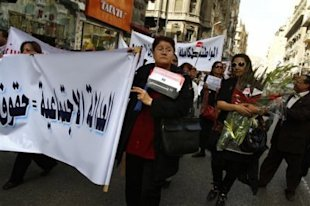 Egyptian women carry banners that read