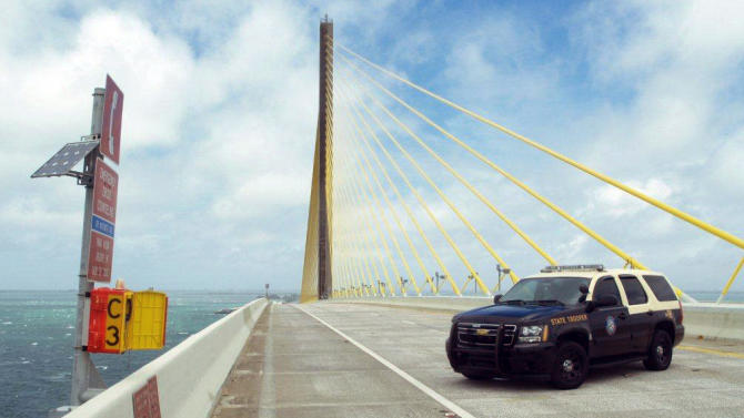 This photo provided by the Florida Highway Patrol shows a patrol car blocking passage on the Sunshine Skyway bridge near St. Petersburg, Fla. Monday, June 25, 2012. The bridge was closed in both directions after wind was reported at  52 miles per hour. Off the coast since the weekend, Tropical Storm Debby raked the Tampa Bay area with high wind and heavy rain in a drenching that could top 2 feet over the next few days and trigger widespread flooding. (AP Photo/Florida Highway Patrol)