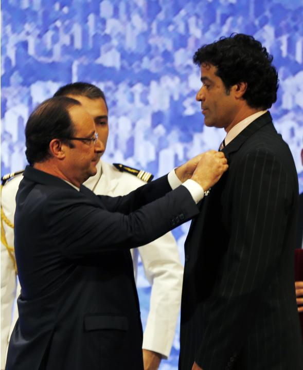 France's President Francois Hollande decorates former PSG soccer star Rai Souza de Oliveira of Brazil with the legion of honor in Sao Paulo