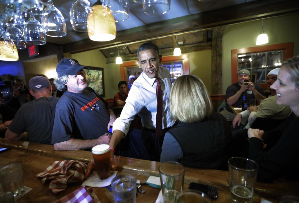President Barack Obama reaches for his beer from the bar as he greets local patrons during an unscheduled visit to the Common Man Merrimack restaurant, Saturday, Oct. 27, 2012 in Merrimack, NH. (AP Photo/Pablo Martinez Monsivais)