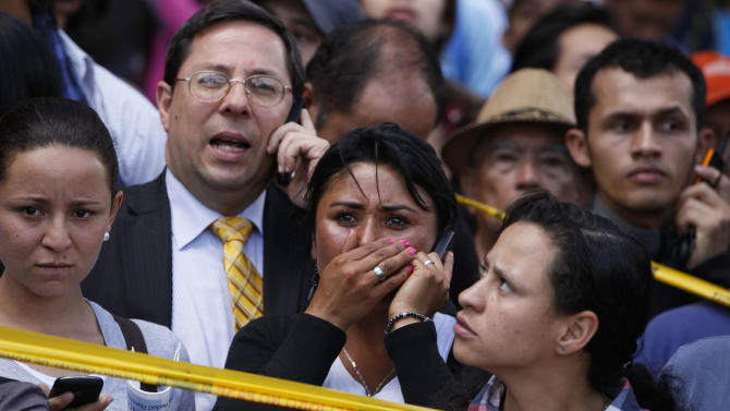 Pedestrians look at the scene after a bomb exploded in Bogota, Colombia, Tuesday, May 15, 2012. Colombian President Juan Manuel Santos says two people were killed in the bomb attack that targeted a former interior minister. (AP Photo/Ricardo Mazalan)