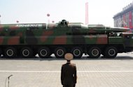 A North Korean soldier stands guard in front of a military vehicle carrying what is believed to be a Taepodong-class missile Intermediary Range Ballistic Missile (IRBM), during a military parade in Pyongyang in April 2012. North Korea has conducted motor tests to improve its long-range missiles after a failed launch in April, a US think tank said Monday after reviewing new satellite images