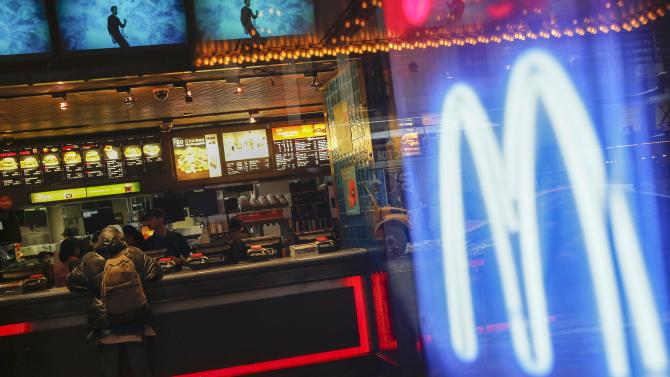 A neon McDonald's Golden Arches is seen as a man waits inside to order at the Times Square location in New York