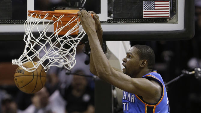 Oklahoma Thunder's Kevin Durant, center, scores over San antonio Spurs' Tim Duncan (21) and Kawhi Leonard (2) during the second quarter of an NBA basketball game, Thursday, Nov. 1, 2012, in San Antonio. (AP Photo/Eric Gay)