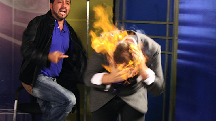 "In this picture released by American magician Wayne Houchin, Dominican TV presenter Franklin Barazarte, left, reacts as Houchin's head burns while taping ""Closer To The Stars"" TV program in Santo Domingo, Dominican Republic, Monday, Nov. 26, 2012. Houchin, of Chico, California, is receiving treatment for burns after the incident where Barazarte lit his head on fire with a flammable cologne. (AP Photo)"