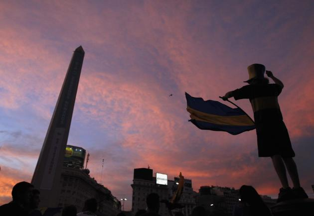 A fan of Argentine soccer team Boca Juniors waves team's flag in front of Obelisco de Buenos Aires during Boca Juniors Fan Day in downtown Buenos Aires