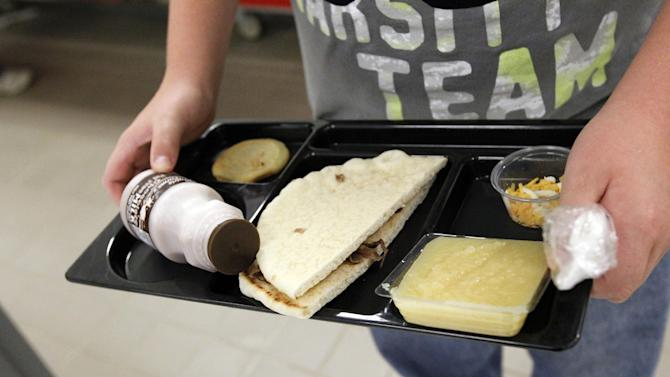 A student at Eastside Elementary School in Clinton, Miss., carries out a noon meal consisting of a flat bread roast beef sandwich, apple sauce, chocolate milk and a cookie, Wednesday, Sept. 12, 2012. The leaner, greener school lunches served under new federal standards are getting mixed grades from students.  (AP Photo/Rogelio V. Solis)
