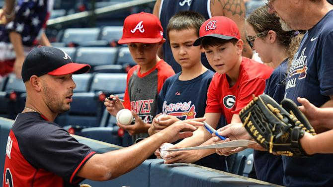 Atlanta Braves relief pitcher David Aardsma, left, gives autographs before a baseball game against the Philadelphia Phillies, Sunday, July 5, 2015, in Atlanta. (AP Photo/Jon Barash)