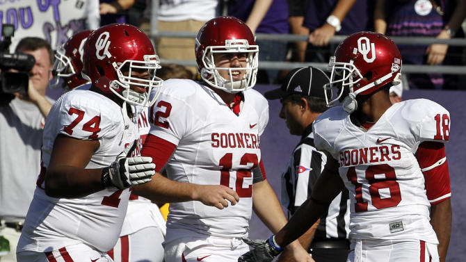 Oklahoma's Adam Shead (74), Landry Jones (12) and Jalen Saunders (18) celebrate Saunders' touchdown reception against TCU in the first half of an NCAA college football game Saturday, Dec. 1, 2012, in Fort Worth, Texas. (AP Photo/Tony Gutierrez)