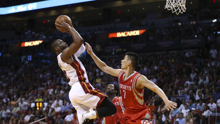 Houston Rockets' Jeremy Lin (7) is unable to block MIami Heat's Dwywane Wade (3) during the first half of an NBA basketball game in Miami, Sunday, March 16, 2014. (AP Photo/J Pat Carter)