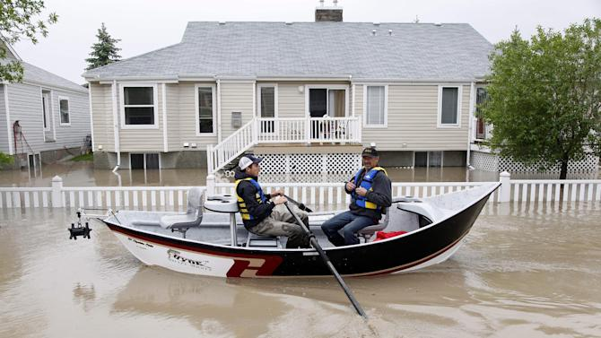 Two men use a fishing boat to rescue residents from a neighborhood after heavy rains caused flooding, closed roads, and forced evacuation in High River, Alta., Thursday, June 20, 2013. Calgary city officials say as many as 100,000 people could be forced from their homes due to heavy flooding in western Canada, while mudslides have forced the closure of the Trans-Canada Highway around the mountain resort towns of Banff and Canmore. (AP Photo/The Canadian Press, Jeff McIntosh )