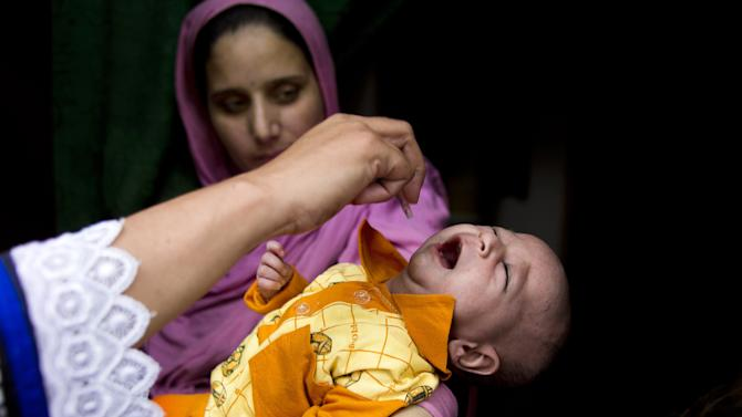 FILE - In this Tuesday, May 6, 2014 file photo, a Pakistani mother looks on as health worker gives a polio vaccine to a child in Rawalpindi, Pakistan. Pakistani officials say hundreds of parents have been arrested in recent days because they refused to allow vaccinators to give their children the polio vaccine. Feroz Shah, a spokesman for the Peshawar district administration, says 471 people have been arrested. (AP Photo/B.K. Bangash, File)