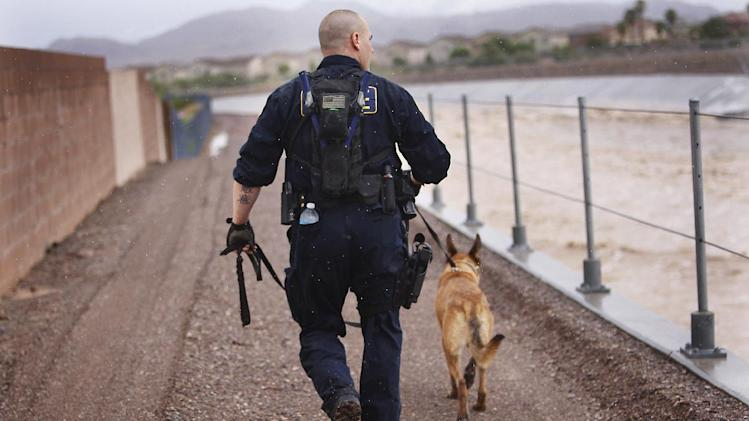 Henderson Police Officer Craig Mancuso and his dog Rony conduct a search of the Duck Creek Channel for 17-year-old Green Valley HIgh School student William Mootz in Henderson, Nev.  on Aug. 22, 2012.  Crews resumed the search Thursday for Mootz, who somehow fell into a drainage wash in Henderson, which had filled quickly after a morning downpour a day earlier.  (AP Photo/Las Vegas Review-Journal, Jason Bean)