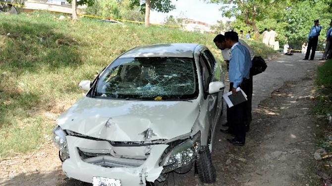 Pakistani police officers examine the car of prosecutor Chaudhry Zulfikar who was targeted by gunmen in Islamabad, Pakistan on Friday, May 3, 2013. Gunmen killed Pakistan's lead prosecutor investigating the assassination of former prime minister Benazir Bhutto as he drove to court in the capital on Friday, throwing the case that also involves former ruler Pervez Musharraf into disarray. (AP Photo/B.K. Bangash)